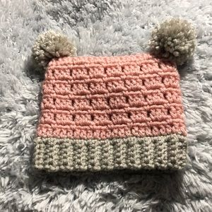 Pink and gray crochet baby hat with pom-poms